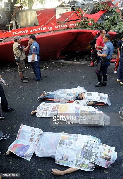 Three of the 22 bodies lay on the road beside the crashed bus that fell from an elevated highway in Manila on December 16 2013 Twentytwo people were...