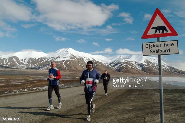 Three of the 36 participants of the Spitsbergen marathon run by a sign warning for polar bears 12 June 2004 on the Svalbard island The world's...