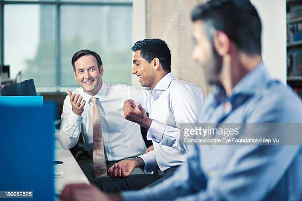 Three office workers at desks, talking