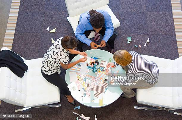 Three office workers making paper flower, elevated view