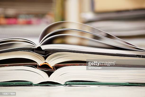 Three open books stacked on top of one another