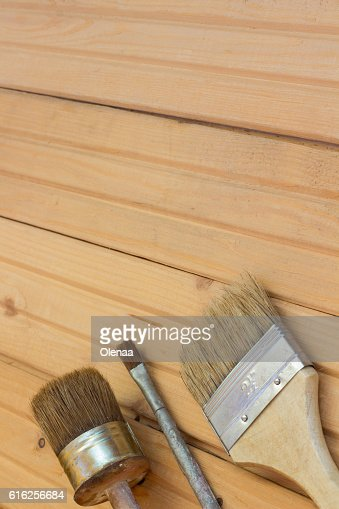 Three paint brushes on a  wooden floor : Foto de stock