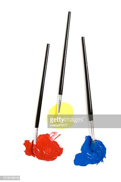 Three paintbrushes dipped in red, yellow and blue