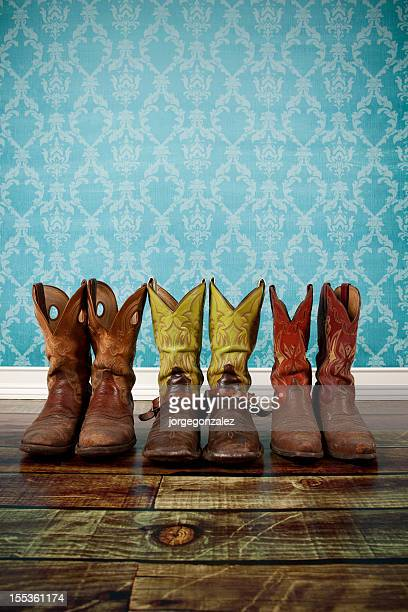Three pair of cowboy boots on wood flooring with blue wall