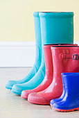 Three Pairs Of Colorful Gumboots In A  Row