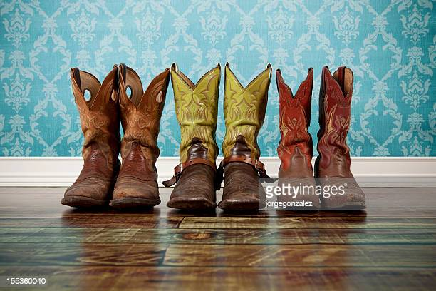 Three pairs of cowboy boots lined up against blue wallpaper