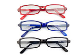 Three pairs of glasses with blue black and red frames on a white background