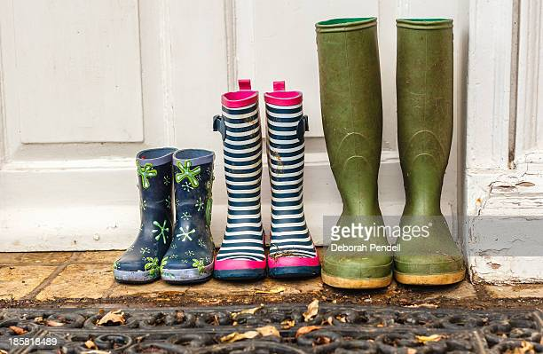 Three pairs of muddy wellies at the door
