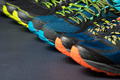 Three pairs of running shoes / exercise trainers lined up in a row on a gym floor with potential text / writing / copy space