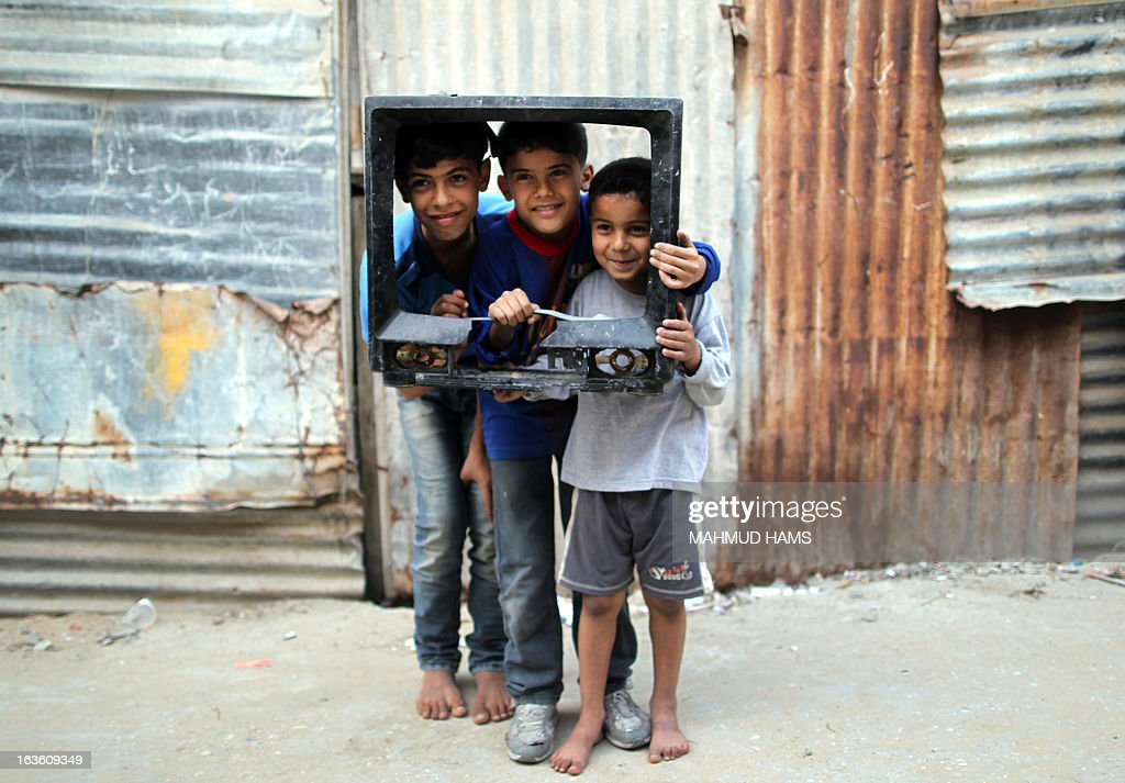 Three Palestinian boys pose inside the frame of a broken television set to have their photo taken in the Mediterranean beachfront al-Shati Palestinian refugee camp, the third largest in the Palestinian Territories, in Gaza City on March 13, 2013.