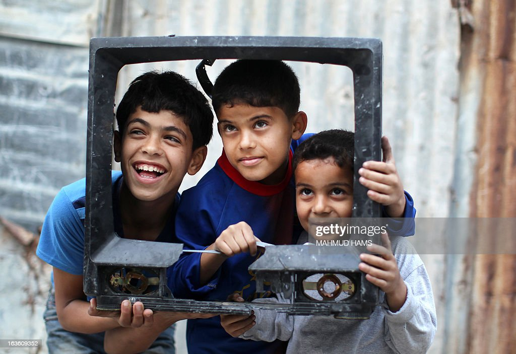 Three Palestinian boys pose inside the frame of a broken television set to have their photo taken in the Mediterranean beachfront al-Shati Palestinian refugee camp, the third largest in the Palestinian Territories, in Gaza City on March 13, 2013. AFP PHOTO / MAHMUD HAMS