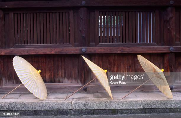 Three paper umbrellas drying on stone platform.