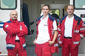 'Three paramedics standing beside ambulance, portrait'