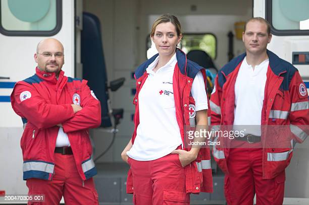 'Three paramedics standing beside ambulance, portrait'