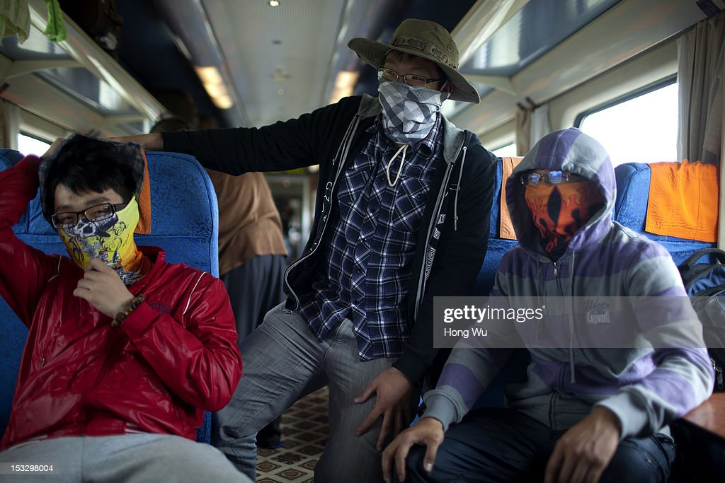 Three passengers wear masks in a train carriage of from Beijing to Lhasa on August 15, 2012 in Damxung, China. After Qinghai-Tibet Railway went into operation on July 1, 2006, connecting China's capital Beijing and Lhasa of Tibet Autonomous Region by 4,064 km of railway line. Passengers and supplies are transported by train on this the world's highest railway to Tibet.