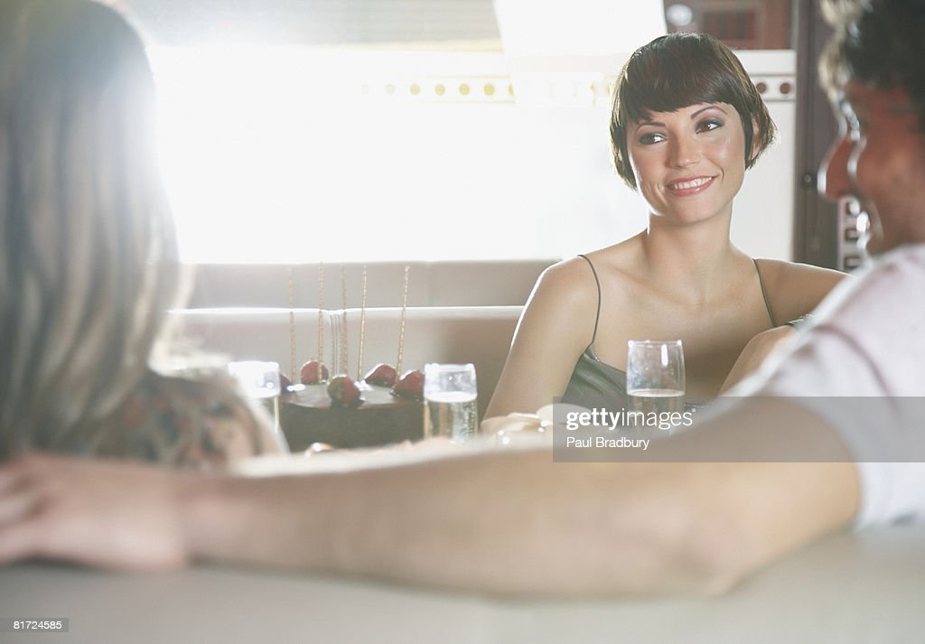 Three people at birthday party in restaurant talking and smiling : Stock Photo
