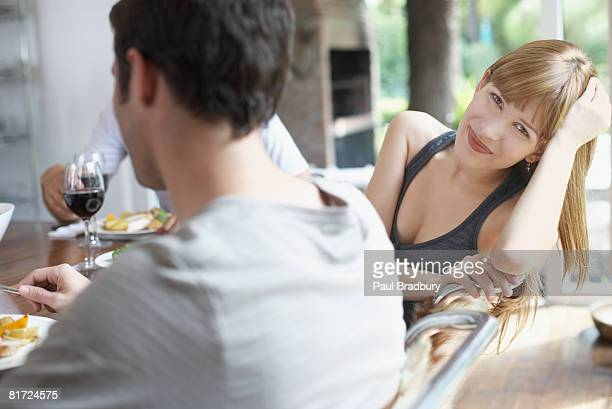 Three people at dinner table focussing on one woman smiling