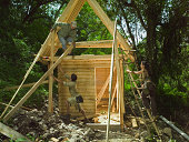 Three people building eco friendly house in forest