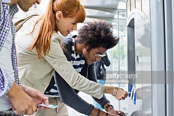 Three people buying tickets for public transport.