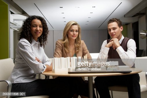 Three people by architectural model on table, smiling, portrait : Stock-Foto