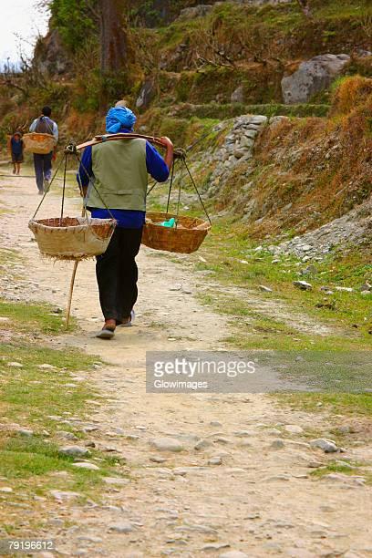 Three people carrying baskets, Annapurna Range, Himalayas, Nepal