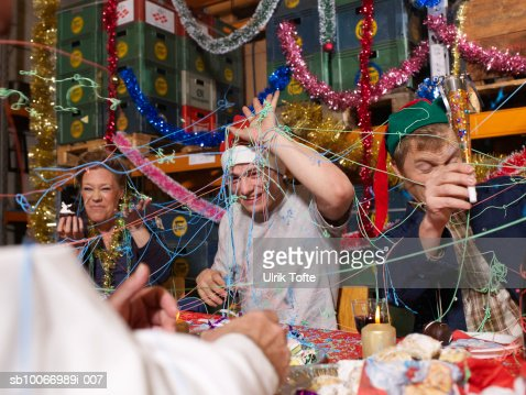 Three people covered in party streamers laughing at charismas table in warehouse : Stock Photo