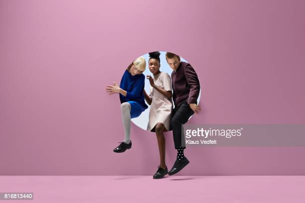 Three people crawling out of round opening in coloured wall