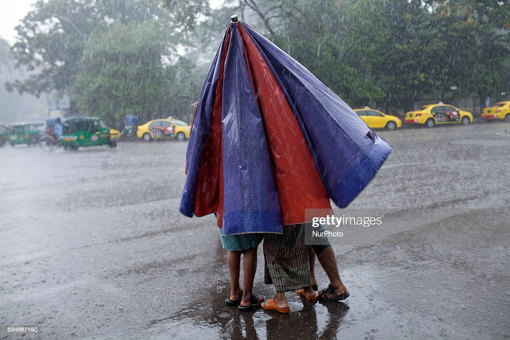Three people crossing the road usingone umbrella during rain in Dhaka, Bangladesh on May 28, 2016.