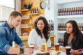 Two women and man tasting craft beer and talking