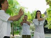 Three people doing tai chi