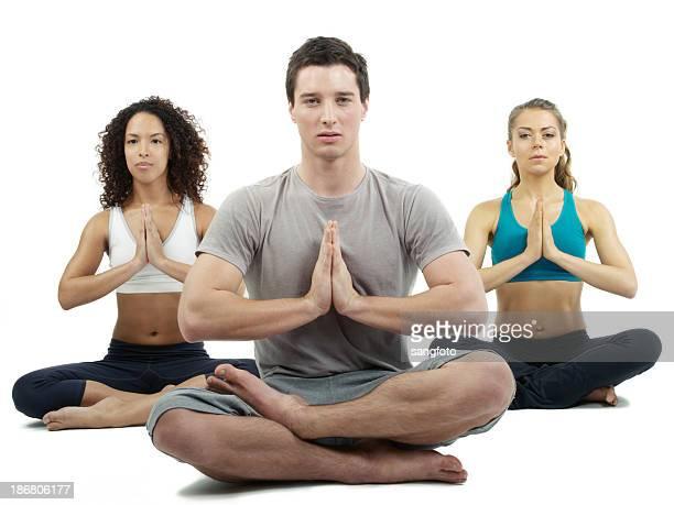 Tres personas haciendo yoga