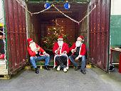 Tres personas armadas con santa ropa sesión en contenedor de carga