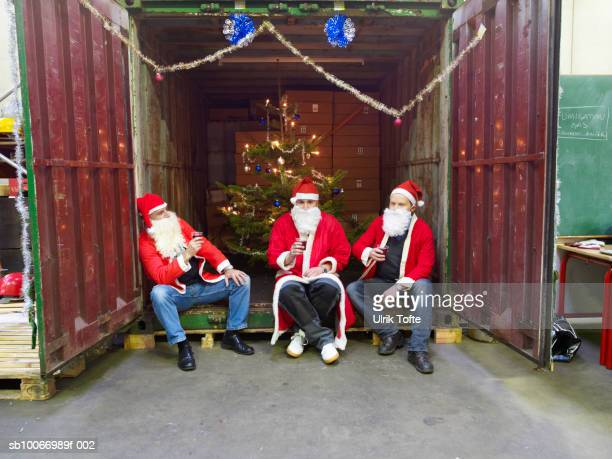Three people dressed in santa clothes sitting in cargo container holding plastic wine cups