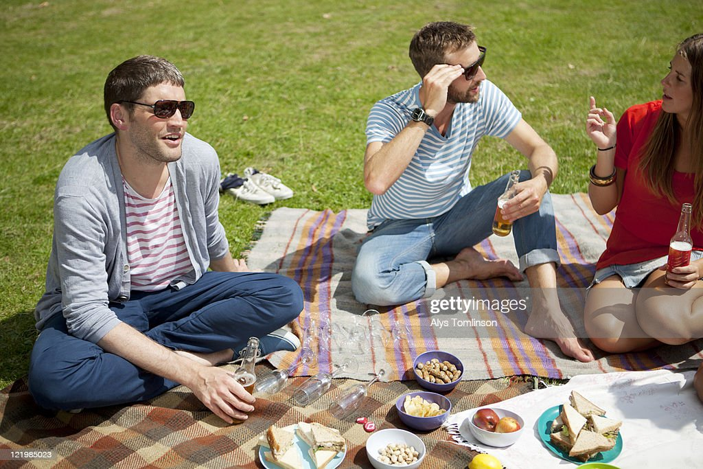 Three People Enjoying a Picnic in a City Park : Stock Photo