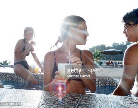 Three people having poolside drinks : Stock Photo