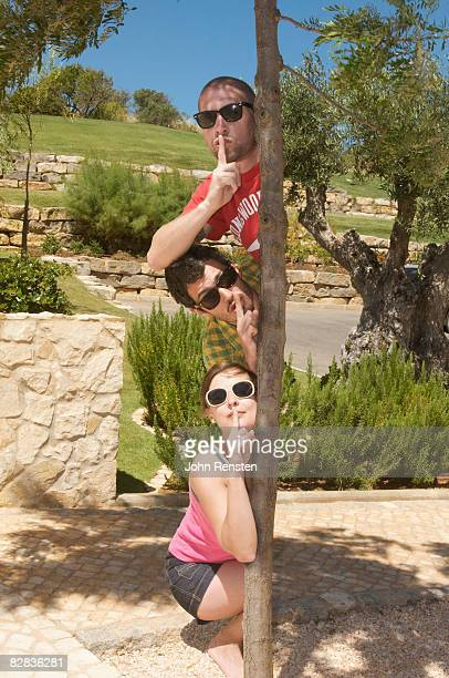 three people hiding behind a tree