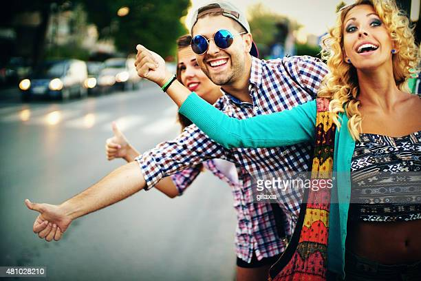 Three people hitchhiking in the city street.
