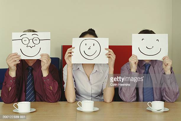 Three people holding hand drawn smiling characters in front of faces