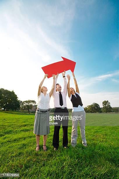Three people holding red arrow