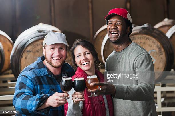 Three people in a microbrewery holding glasses of beer