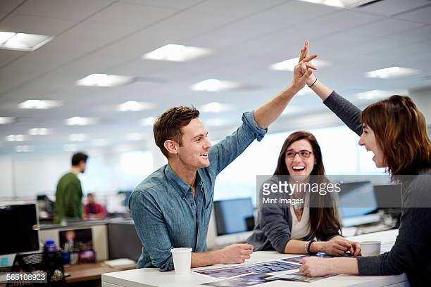 Three people in an office looking at photographs and making a high five gesture.