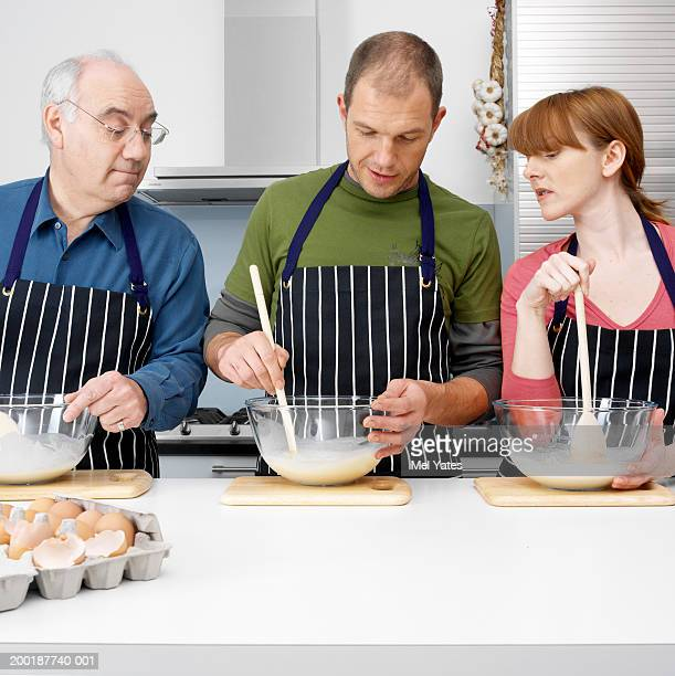 Three people in kitchen, mixing ingredients in bowls
