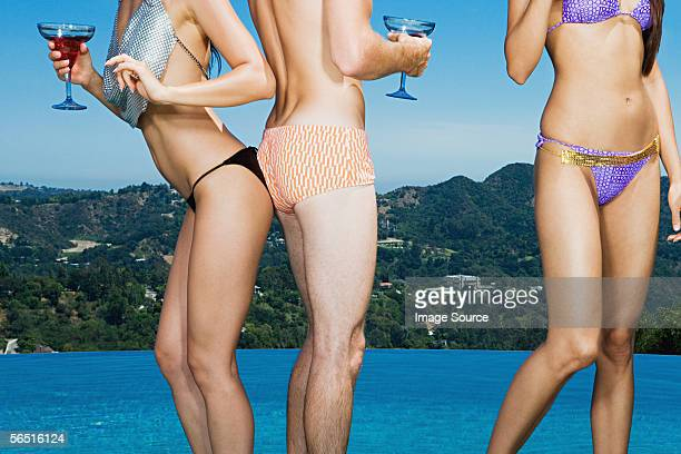 Three people in swimwear with cocktails