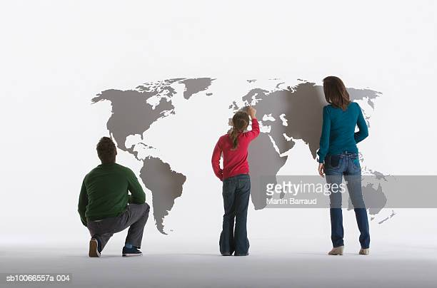 Three people including girl (8-9) looking at map of world on clear acrylic sheet, rear view