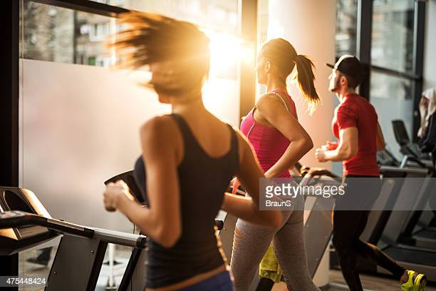 Three people jogging on treadmills in a gym.
