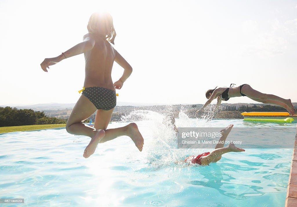 Three people jumping into swimming pool