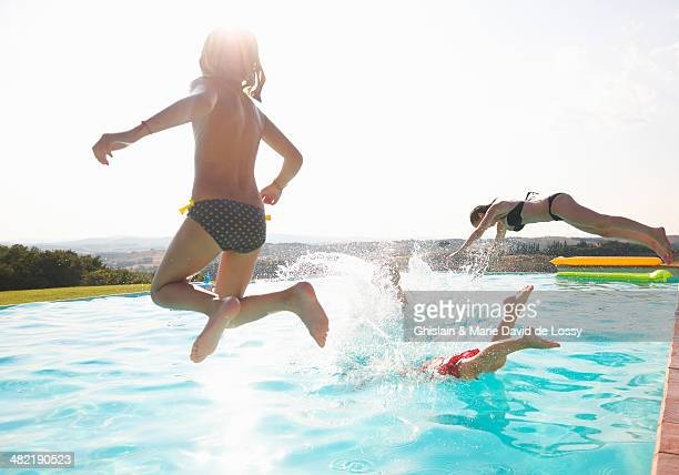 Three people jumping into swimming pool