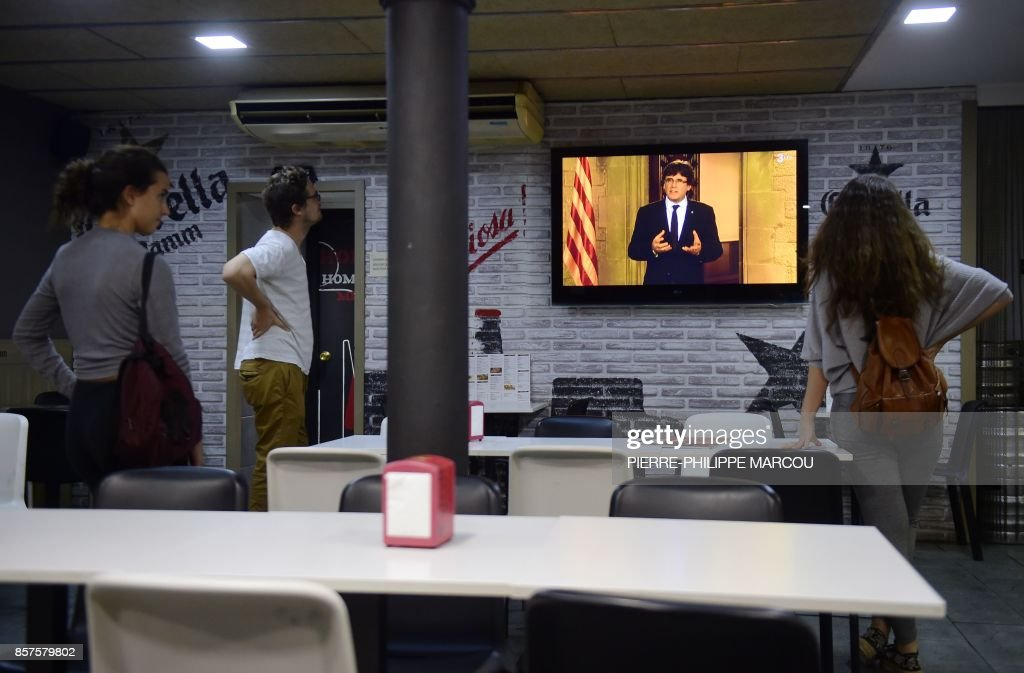 Three people listen to Catalan president Carles Puigdemont's institutional statement on a television set in a bar in Barcelona on October 4, 2017. Catalonia could declare independence on October 9, a regional government source told AFP, as a crisis escalates between Madrid and separatist leaders over an illegal independence referendum. /