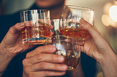 Three people make a toast with whiskey