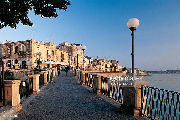 Three people on a bridge at the waterfront Ortygia Siracusa Sicily Italy